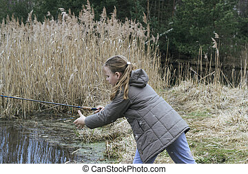 Beautiful little girl fishing with spinning on the river.
