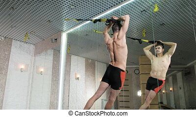 Man is engaged in trx exercises in the studio