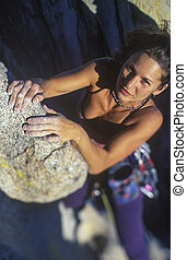 Climber on the edge. - Female climber struggeling up a sheer...