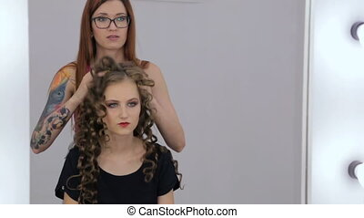 2 shots. Hairdresser finishing hairstyle for teen girl - 2...