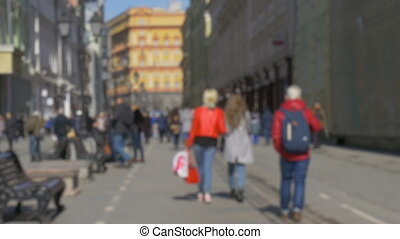 Blurred intentionally, people are walking along the...
