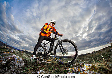 Bottom view photo of cyclist in orange jacket standing with his bike on the rock against blue sky with clouds.