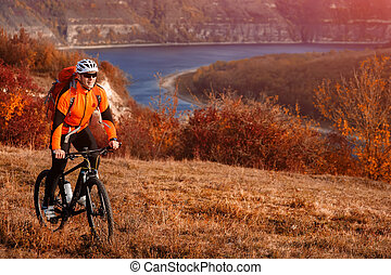 Cyclist in orange jacketr riding bike on the hill under...