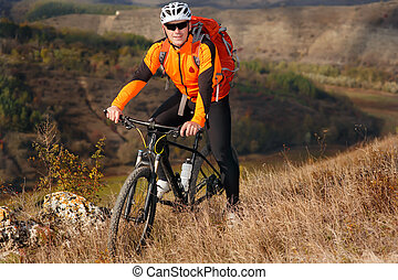 Cyclist in the orange jacket standing with his bike on the top of a hill against beautiful landscape.