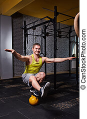 Cross fit fitness man standing on one leg and balance on the kettlebells in the gym against brick wall.