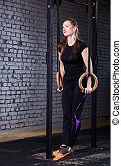 Young fit woman in the sportwear doing pull-ups on gymnastic rings against brick wall in the cross fit gym.