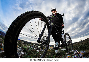 Bottom view photo of cyclist in the black sportwear standing with his bike on the rock against blue sky with clouds.