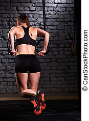 Rear view photo of young fit woman doing pull-ups with rings against brick wall in the cross fit gym.