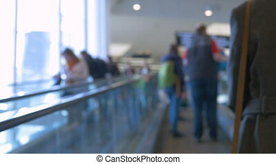 Buyers go down and climb the escalator in the mall. Blurred...