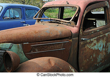 Old Cars in the Junkyard - Old and rusty cars in the...