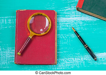 Magnifying glass with text book on wood