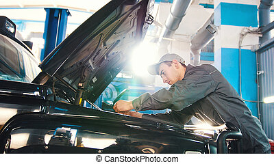 Mechanic in car service - repairing in engine compartment...