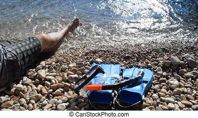 The man lying next to the diving equipment