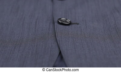 Close-up of buttons on a blue suit. Dolly shot. Fashion...