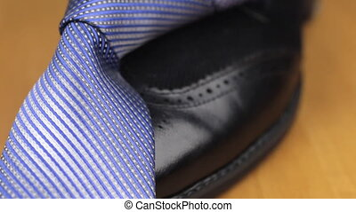 Blue knotted tie lies on a black men's shoes. Dolly shot....