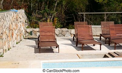 Wooden deck chairs, dark wood in empty swimming pool -...