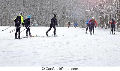 Equipped skiers skiing on piste with ski poles under heavy...