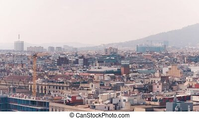 Barcelona rooftops and distant mountains, Spain. 4K long focus pan shot