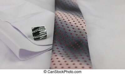 Close-up of a pink tie and cufflinks lying on a white shirt....