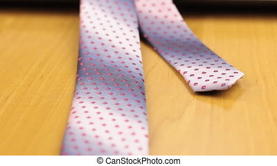 Close-up of a tie and cufflinks lying on a laptop. Dolly...