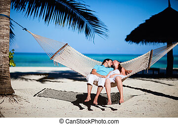 Romantic couple relaxing in hammock - Young romantic couple...