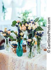 Cream and blue flowers in vases on a table with a lace...