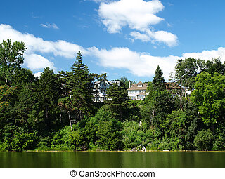 riverbank - Peaceful scenic view of riverbank with houses on...