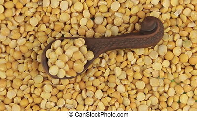 Rotation and zoom of peas in a clay spoon lying on the background of peas seeds.