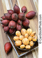 Salak or Salacca zalacca tropical fruit in wooden plate -...