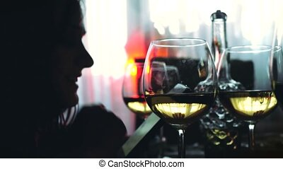 Silhouette of woman uses smartphone and glasses of white wine sits at served table. 3840x2160