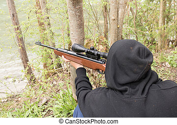 Terrorist sniper shooting with his weapon.