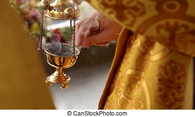 The priest lights incense in the censer, incense smolders...