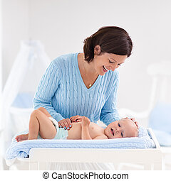 Mother changing diaper to baby boy - Mother and baby change...