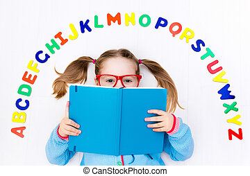 Child learning letters of alphabet and reading - Happy...