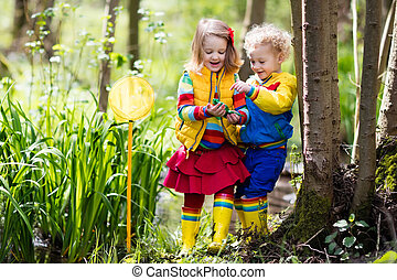 Children playing outdoors catching frog - Children playing...