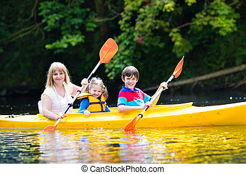Family enjoying kayak ride on a river - Happy family with...