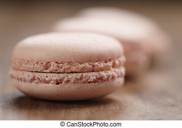 closeup shot pastel colored macarons with rose flavour on wood table