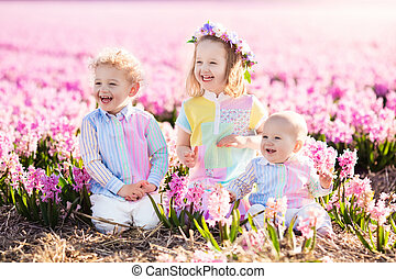 Kids playing in flower field - Three children playing in...
