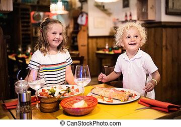 Kids eating pizza in Italian restaurant - Kids eat pizza,...