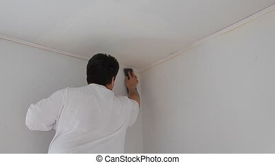 Room repair, hand sanding the wall with a sanding sponge...