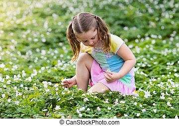 Child in spring park with flowers