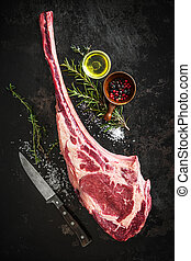 Dry aged raw tomahawk beef steak with ingredients for...