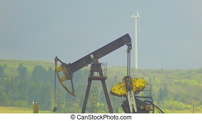 oil well pumpjack and Wind power plant in background with gray sky