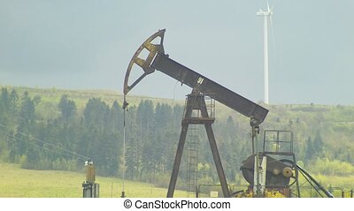 oil well pumpjack and Wind power plant in background with...