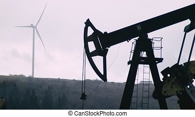 oil well with pumpjack and Wind power plant in background -...