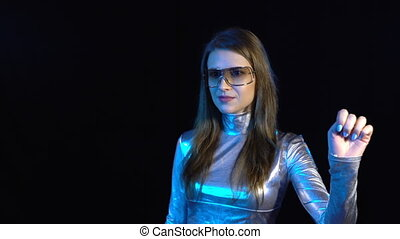 Cyber young woman in silver clothing turning over the...