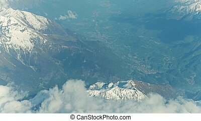 Snowy montain peaks and distant alpine towns in a valley -...