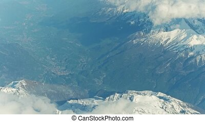 Snowy montain peaks and distant alpine towns in a valley. 4K...
