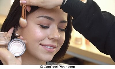 Professional make up artist applying cosmetic on face of cute teen girl for skin care and health complexion