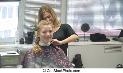 Portrait of a young woman in a beauty salon: creating a magnificent setting from curls. A blonde in a hairdresser does a beautiful hairstyle. Hair care and creating an image.